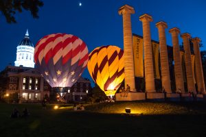 A Mizzou and American flag hot air balloon sit between the columns and Jesse Hall all lit up during Welcome Week 2018.